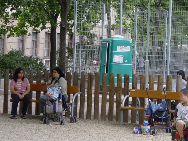 Frauen und Kinder sitzen auf einer PArkbank